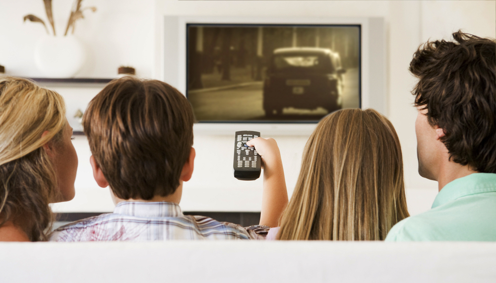 Familie schaut überspielten Super 8 Film aus Berlin auf dem Fernseher